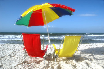 Beach scene with beach chairs and unbrella.