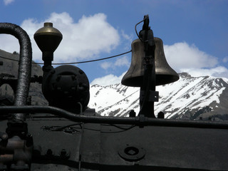 Bell atop a steam locomotive running through the mountains