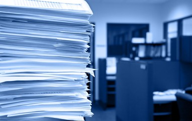 Pile of papers on a background of office cubicles