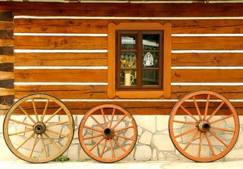 Wooden wheels at cottage wall