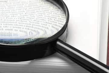 magnifying glass on a book - close-up