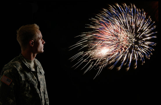 A soldier stands watching fireworks