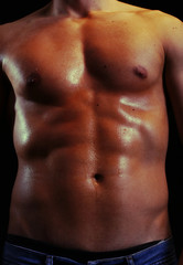 Handsome shiny naked muscular male body isolated on black