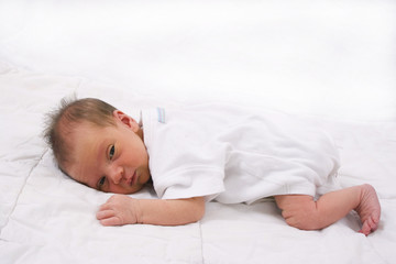 Beautiful little newborn baby with open eyes.