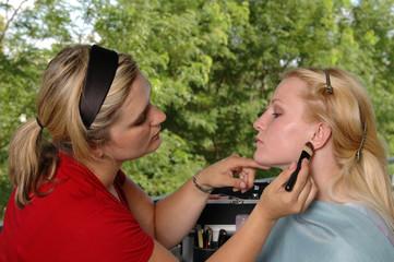 A makeup artist applying blush to a model
