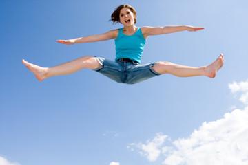 junges, schönes Mädchen springt unter dem Himmel