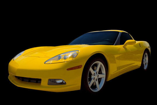 A yellow sports car isolated on a black background.