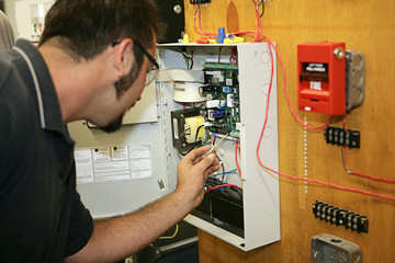 electrician wiring a fire alarm system