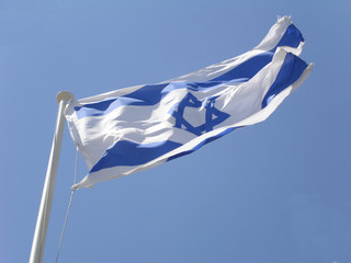 Israeli flag swaying in the wind in a clear blue sky