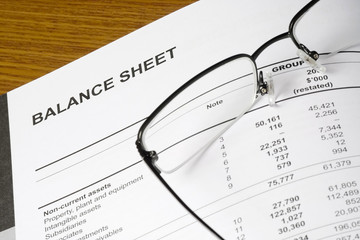Balance sheet of a financial report with spectacles..