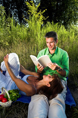 couple reading a book outdoor at sunset