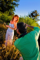 couple playing outside on a field taking pictures