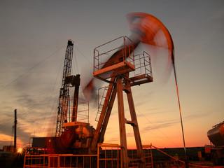 Silhouette of swinging oil pump in evening sky