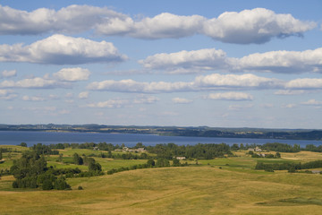 Landscape of fields and lake with clouds, captured in Latvia