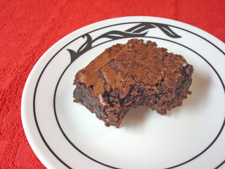 Brownie on a white plate set on a red placemat