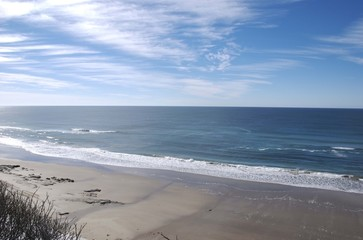 Stretch of beach and ocean with blue sky and clouds