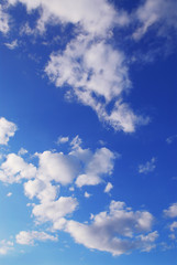 Background if bright blue sky with white fluffy clouds