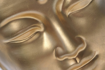 Diagonal close up of golden buddha face.