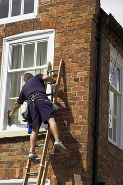 Man balancing on a ladder to clean windows