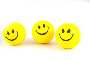 3 yellow balls whit smile on a white background