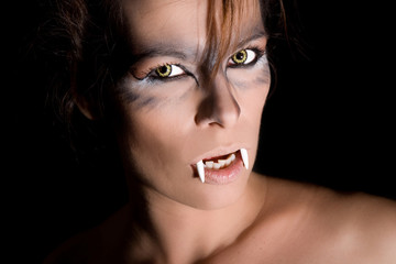 Dangerous looking female vampire on black background