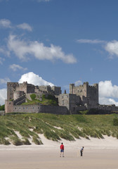 Fototapete - Bamburgh Castle and beach at low tide in Northumberland, England