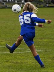 soccer girl giving the football a good kick