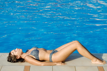A photo of woman lying on the poolside