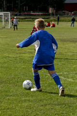 kid dribbling with the ball at a soccer game