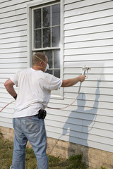 Contractor spray painting exterior of house