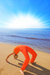 Blond girl shows some yoga moves on the beach