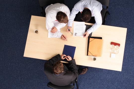 men reading resume - job interview