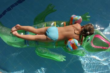 Girl swimming on crocodile