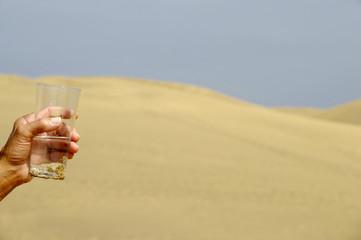 Hand and fresh water in desert