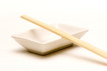 empty soy sauce dish with a couple of chopsticks
