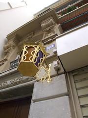 Lanterne dorée accrochée à un mur de pierre