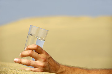 Hand and water in desert