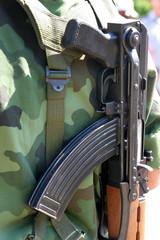 details of man at arms with kalashnikov