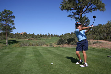Young male golfer about to tee off on beautiful golf course