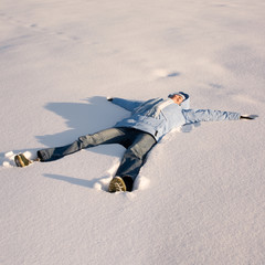 Happy young girl  lying in the snow