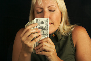 Attractive Woman Smells Her Stack of Money.