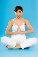 A young Asian woman in white practising yoga on blue background
