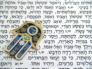 Blue Hamsa kabala good luck charm on Hebrew bible