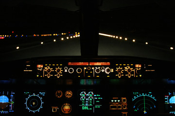 aircraft landing at night with runway ahead