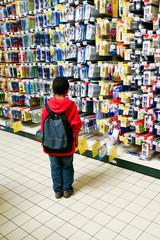Petit garçon de dos au milieu de fournitures scolaires