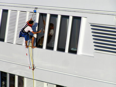 The cleaner who washes a window of the exterior of a yacht