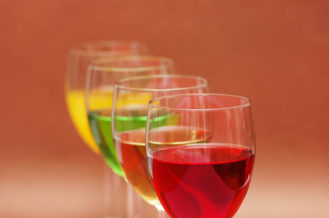Glasses with drinks of various colours on  biege background
