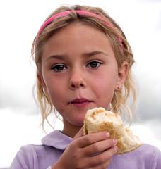 Little girl eating a bagel