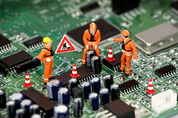 Technicians working on electronics or motherboard