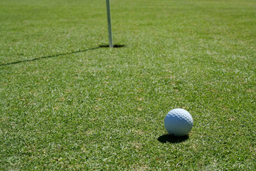 Golf Ball on green near hole